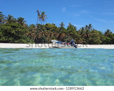 Boat on a white sandy beach with tropical vegetation, viewed from water surface - stock photo