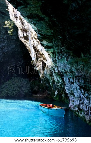 boat on an underground turquoise lake in a cave