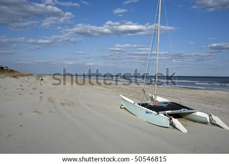 Boat on beach with ocean - stock photo