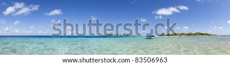 Boat on blue lagoon front of a paradise island panoramic view - stock photo