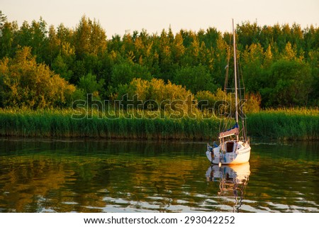 Boat on river with trees on background - stock photo