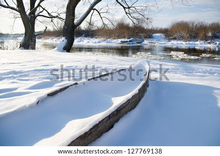 Boat on the bank of the winter river