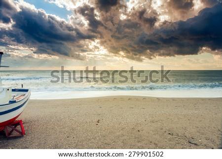 Boat on the beach near Almeria at sunset time. Cabo de Gata Nijar Natural Park, Almer���a. Spain. Andalusia - stock photo