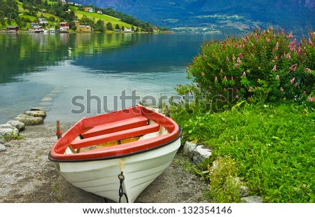 Boat on the beach of Norwegian village Olden in Norwegian fjords. - stock photo