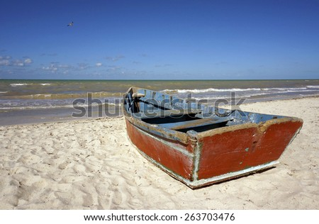 Boat on the beach under a clear blue sky.