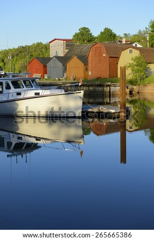 Boat Reflecting in Calm Water at Dock - stock photo