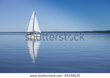 Boat reflecting in the water, sailing in calm, blue water. Swedish flag on boat