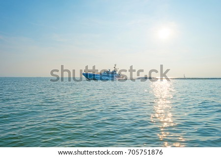 Boat sailing on a lake at sunset in summer