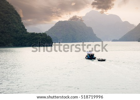 Boat sailing on Halong Bay, UNESCO world heritage site. Limestone islands protrude from the water.