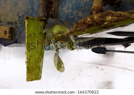 Boat stern hull and propeller pressure water cleaning on beached ship - stock photo