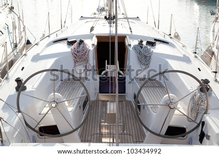 boat stern with double steering wheel and sailboat ropes - stock photo