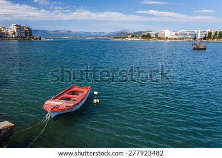 Boat tied at small harbour in Chalkida, Evia, Greece against a cloudy sky with the city buildings in the background - stock photo
