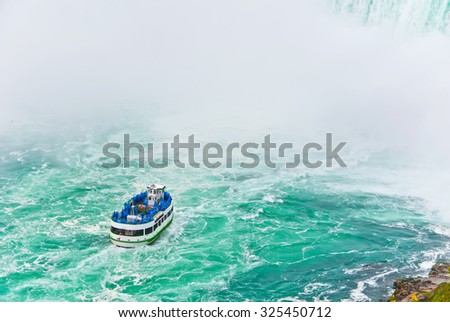 Boat tour at Niagara Falls with spraying water - stock photo