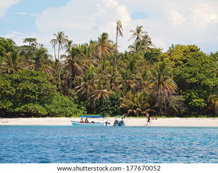 Boat tour with tourists on a tropical beach of the national park of Bastimentos, Zapatillas islands, Caribbean sea, Panama - stock photo