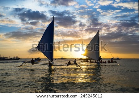 Boat trip at sunset under sails