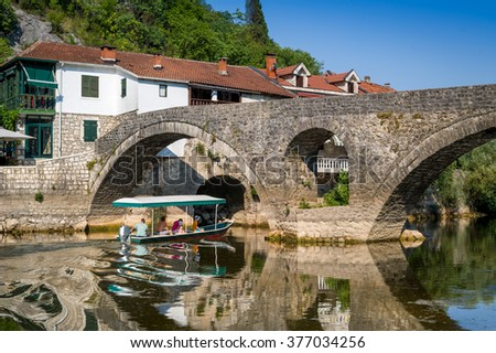 Boat trips of Rijeka Crnojevica town. Excursion boat is going under the old stone bridge. Crnojevica is very popular touristic destination of Montenegro.