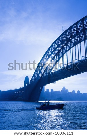 Boat under Sydney Harbour Bridge at dusk with view of distant skyline and harbour in Sydney, Australia. - stock photo