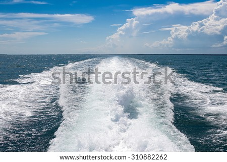 Boat wake, trail on water or sea after high powered boat with blue cloudy sky.