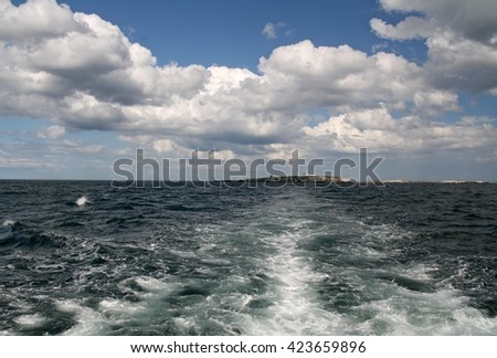 Boat wash on deep blue sea leading from Coquet Island and blue sky with white clouds.