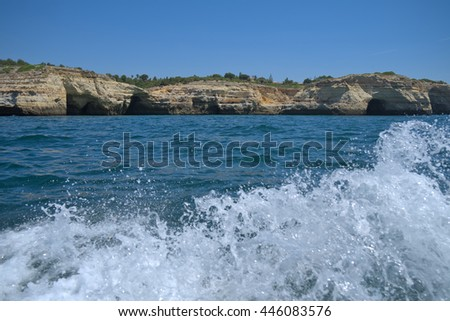 Boat water splash while visiting the cliffs and caves in Carvoeiro. Algarve, Portugal - stock photo