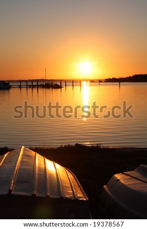 boat with sunset in back ground - stock photo