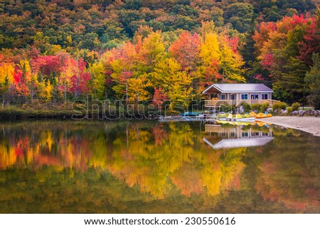 Boathouse and fall colors reflecting in Echo Lake, in Franconia Notch State Park, New Hampshire. - stock photo
