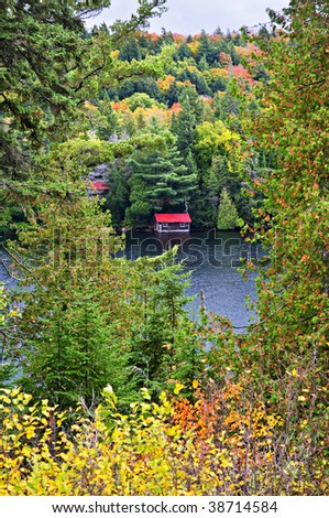 Boathouse on lake through fall forest with colorful trees - stock photo