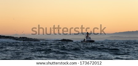 Boating at sunset in Atlantic ocean, South Africa  - stock photo