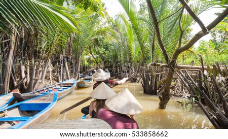 Boating on a dirty river with conical hats in the Mekong Delta, Vietnam