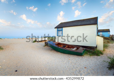 Boats and beach huts at Mudeford Spit near Christchurch in Dorset - stock photo