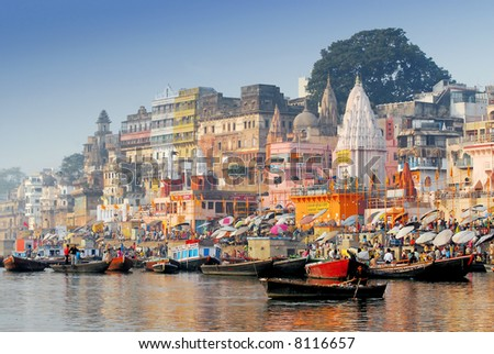 boats and reflection in water at the main ghat in varanasi on a sunny day - stock photo