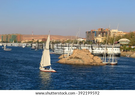 Boats docked and fellucas sailing along the shore of the Nile River at Aswan, Egypt - stock photo