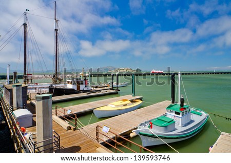 Boats docked at Fisherman's Wharf with Alcatraz in the background. - stock photo