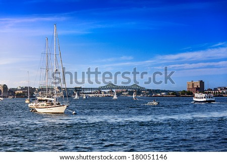 Boats in busy Boston Harbor with the Tobin Bridge in the background - stock photo