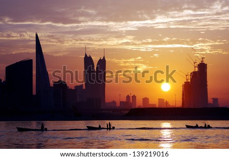 Boats in queue and Bahrain skyline at sunset - stock photo