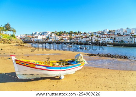 Boats in warm sunset light on the beach in Portimao, Portugal - stock photo