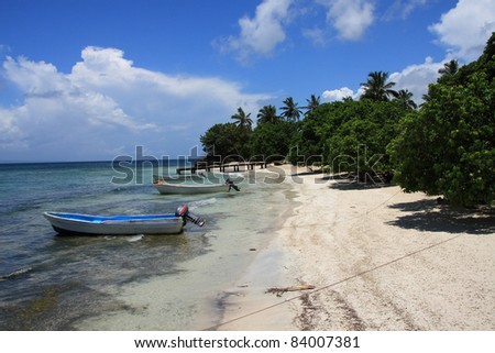 Boats moored on a deserted Caribbean beach - stock photo