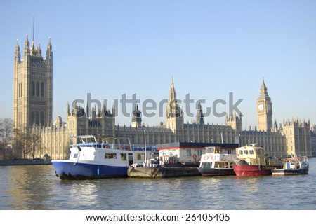 Boats moored on the River Thames in front of the Houses of Parliament in London, England - stock photo