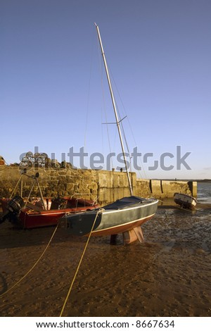Boats moored up at Beadnell Harbour at sunset. Englands only easterley facing harbour on the east coast of England - stock photo