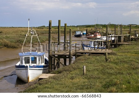 Boats on a channel of water on the North Norfolk coast - stock photo