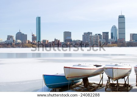 boats on frozen charles river overlooking boston skyline in the winter - stock photo