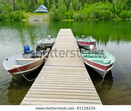 Boats on lake over a waterfront house. - stock photo