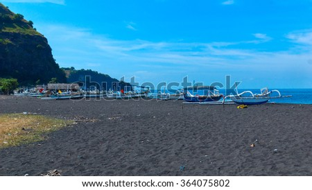 Boats on the beach of black sand on the island of Bali in Indonesia. Summer sunny day. - stock photo