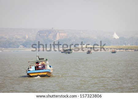 Boats on the Irrawaddy River, the Mingun Pahtodawgyi pagoda is visible in the background, focus on foreground, Mingun, Sagaing Region, Burma, Myanmar - stock photo