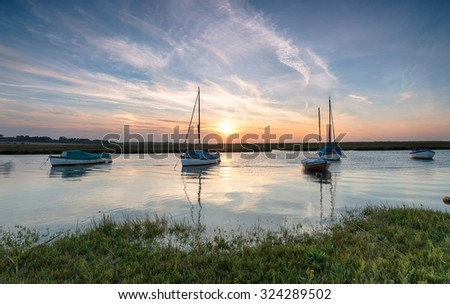 Boats on the river Glaven at Blakeney on the north coast of Norfolk - stock photo