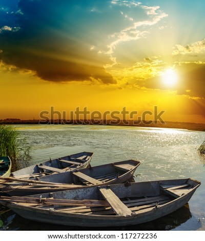 boats on water under sunset - stock photo