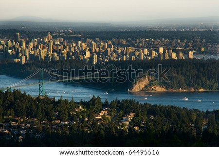Boats pass underneath Lions Gate Bridge in Vancouver with Downtown skyline behind. - stock photo