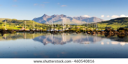 Boats shelter in Portree Bay on Scotland's Isle of Skye, with the Cuillin mountains providing the backdrop, reflected in the blue waters.