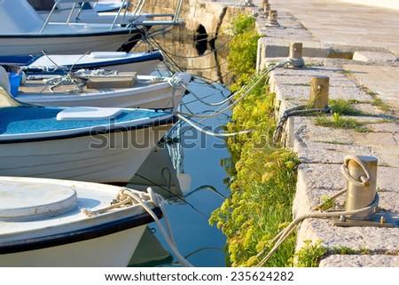 Boats tied at the marina - bow, ropes and mooring bollard view - stock photo