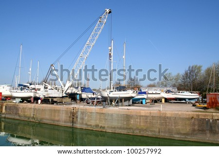 Boatyard. Several boats on the quayside . A crane stands by the waters edge.